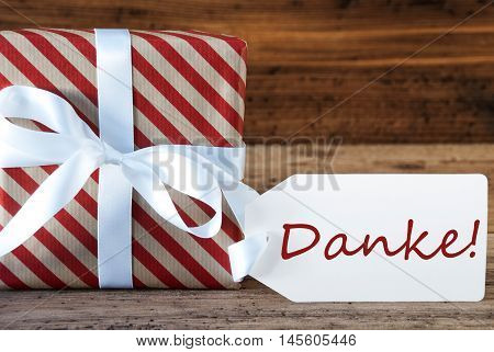 Macro Of Christmas Gift Or Present On Wooden Background. Card For Seasons Greetings, Best Wishes Or Congratulations. White Ribbon With Bow. German Text Danke Means Thank You