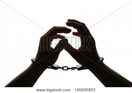 Black silhouette of man hands in handcuffs on light background