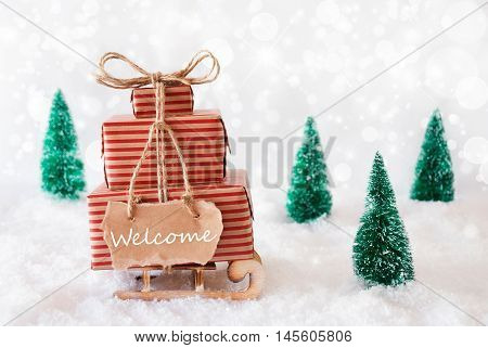 Sled With Christmas Gifts Or Presents. Snowy Scenery With Snow And Trees. White Sparkling Background With Bokeh Effect. Label With English Text Welcome