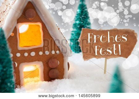 Gingerbread House In Snowy Scenery As Christmas Decoration. Trees And Candlelight For Romantic Atmosphere. Silver Background With Bokeh Effect. German Text Frohes Fest Means Merry Christmas