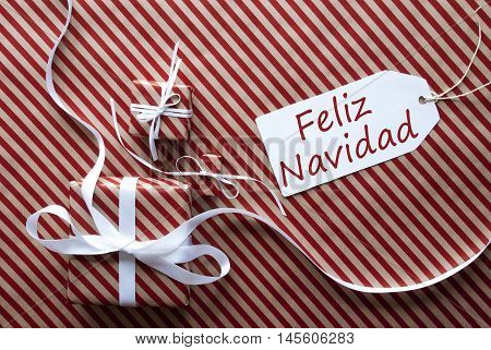 Two Gifts Or Presents With White Ribbon. Red And Brown Striped Wrapping Paper. Christmas Or Greeting Card. Label With Spanish Text Feliz Navidad Means Merry Christmas