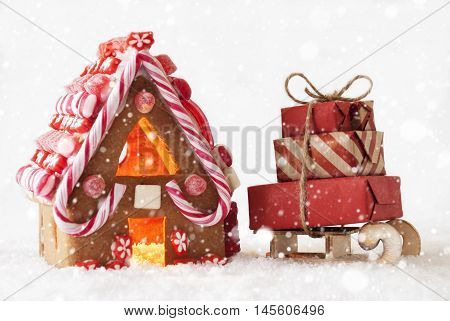 Gingerbread House In Snow As Christmas Decoration. Candlelight For Romantic Atmosphere. White Background With Snowflakes. Sled With Gifts Or Presents