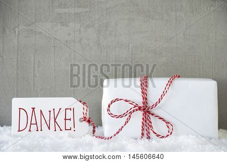 One Christmas Gift Or Present On Snow. Cement Or Concrete Wall As Background. Modern And Urban Style. Card For Birthday Or Seasons Greetings. Label With German Text Danke Means Thank You