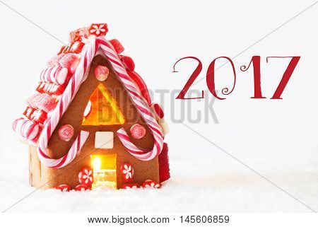 Gingerbread House In Snowy Scenery As Christmas Decoration With White Background. Candlelight For Romantic Atmosphere. Text 2017 For Happy New Year