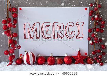 Label With French Text Merci Means Thank You. Red Christmas Decoration Like Balls On Snow. Urban And Modern Cement Wall As Background With Snowflakes.