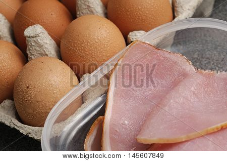 Uncooked bacon and eggs to prepare a meal