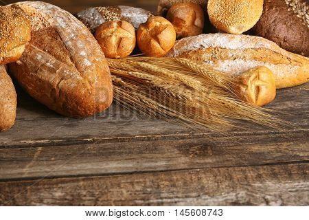 Variety of wheat bread and spikes on old wooden table