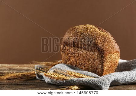 Loaf of rye bread with spikes on gray napkin