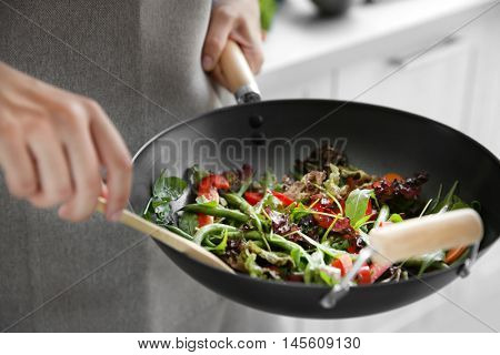 Female hand mixing vegetables in pan closeup