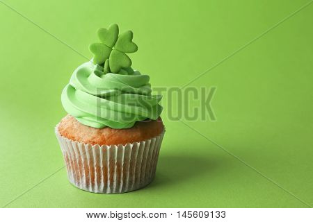 Tasty cupcake with clover on green background. Saint Patrics Day concept