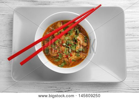 Tasty chicken curry in plate and chopsticks, closeup