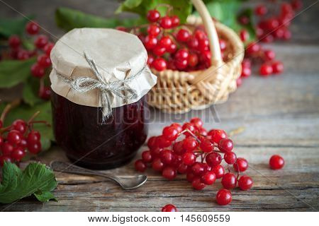 Jar Of Guelder Rose (red Viburnum) Jam And Basket With Red Healthy Berries On Background.