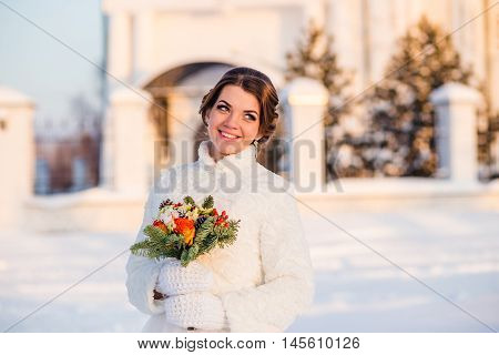 happy and beautiful bride smiles and holds bouquet of orange roses at winter outdoors.