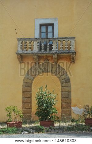 Old balcony of stone on yellow house in Italy with stone arch including