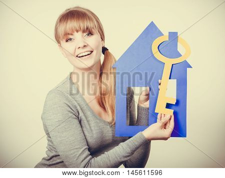 Security safety ownership protection lock concept. Young lady holding housing symbols. Smiling girl showing key building models.