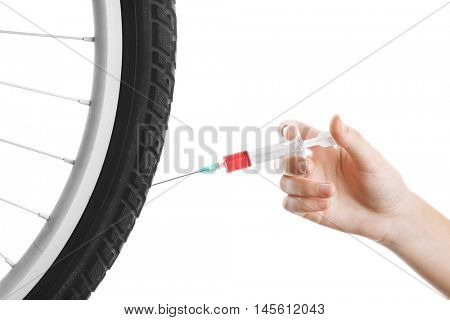 Female hand with syringe and bicycle wheel. Doping in sport concept