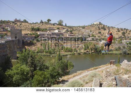 Toledo Spain - August 28 2016: Zip line attraction beside Saint Martin bridge over Tagus river Toledo Spain