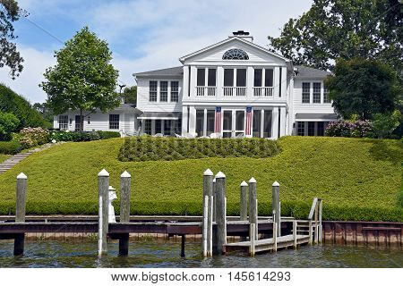 elegant white house with flags and dock on river
