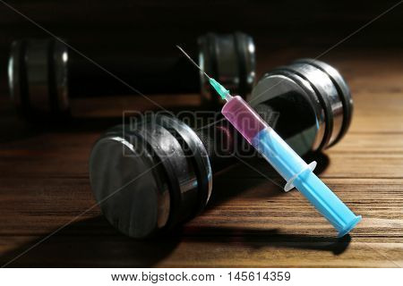 Syringe and dumbbells. Doping in sport concept