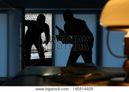 Armed thieves entering a house
