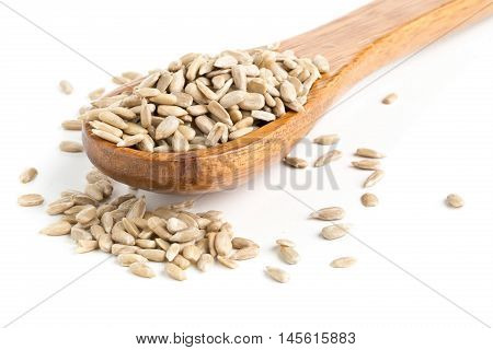 Natural shelled sunflower seeds in wooden spoon over white background