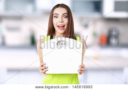 Young beautiful woman with scales on blurred kitchen interior background.
