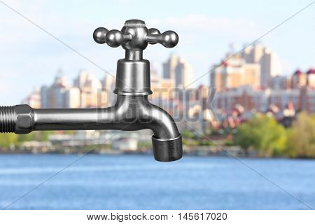 Conservation water concept. Metal faucet on cityscape background.