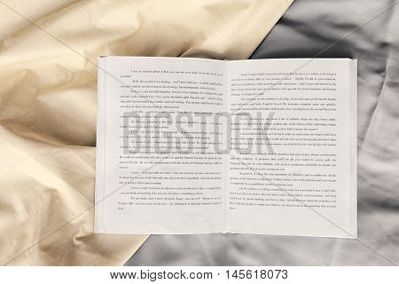 Opened book on crumpled sheet