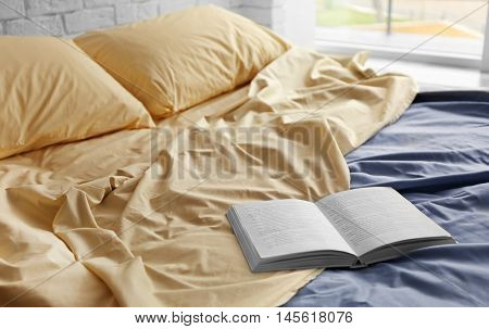 Opened book on crumpled bed in room