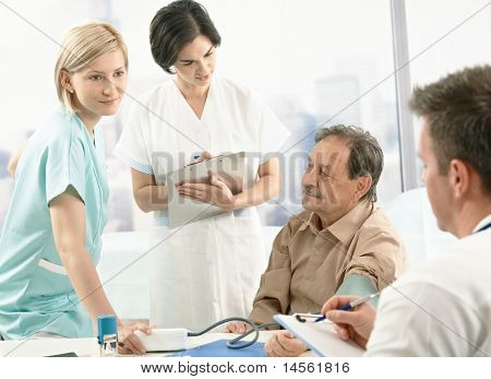 Medical team measuring blood pressure of senior patient, nurse assisting, doctors taking notes on clipboard.?