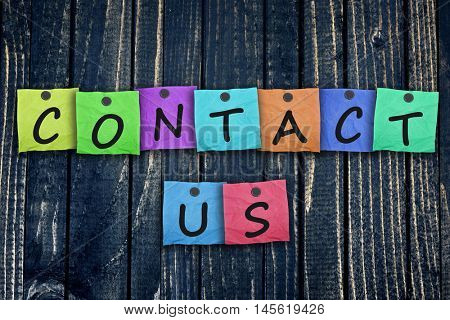 Contact Us message post on wooden wall close-up