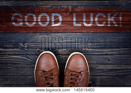 Good Luck message and sport shoes on wooden floor