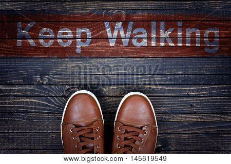 Keep Walking message and sport shoes on wooden floor