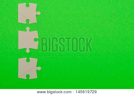 White puzzle pieces isolated on a green background