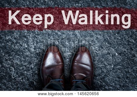Keep Walking message on asphalt and business shoes