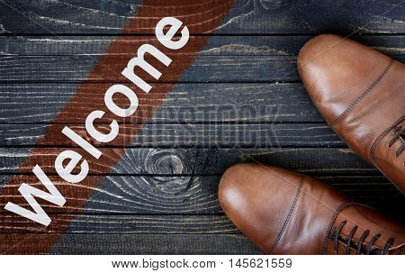 Welcome message and business shoes on wooden floor