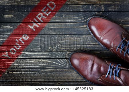 You're hired message and business shoes on wooden floor