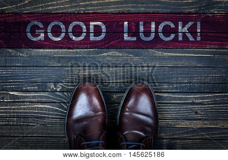 Good luck message and business shoes on wooden floor