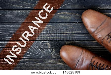 Insurance message and business shoes on wooden floor