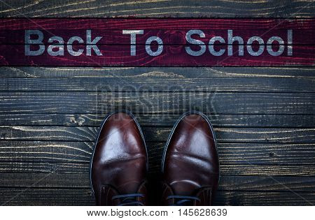 Back to School message and business shoes on wooden floor