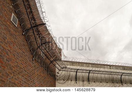 Looking up at the tall wall surrounding Reading Prison with razor wire coiled around the top to deter escape. Berkshire. The prison once had playwright Oscar Wilde as an inmate..