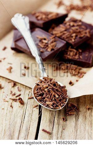 Grated dark chocolate in a spoon on kraft paper, macro.