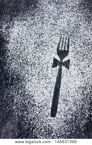 Fork imprint with a bow made in icing sugar on a stone table.