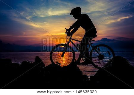 Silhouette of bicyclist riding the bike on a rocky trail at seaside on colorful sunset sky background. Active outdoors lifestyle for healthy concept. Cross process.
