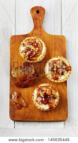 Tartlets with ricotta cheese decorated nuts, apple and caramel. Great homemade dessert. Top view, flat lay.
