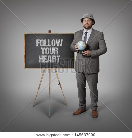 Follow your heart text on blackboard with businessman holding globe in hands