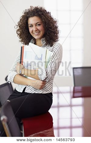 Pretty Secretary With Charts Smiling At Work
