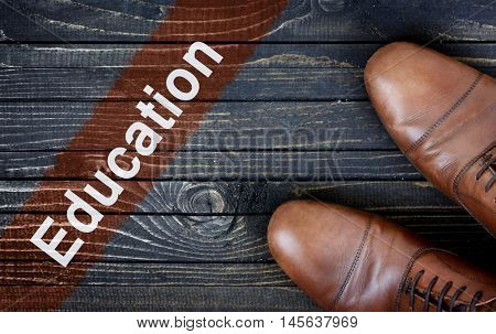 Education message and business shoes on wooden floor