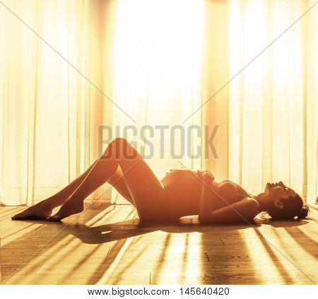 Pregnant woman on window background