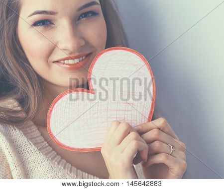 Portrait of young beautiful woman showing gift card. Valentine's Day